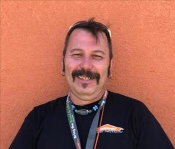Don Poses for his employee photo against an orange background