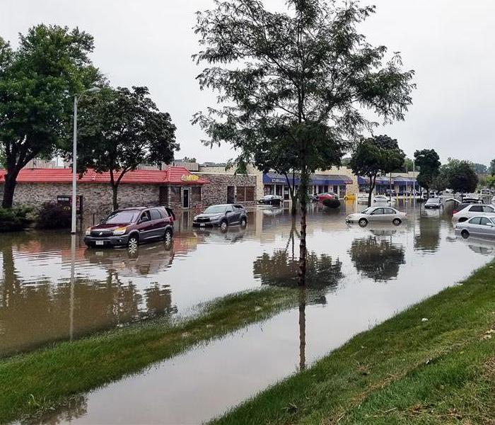 a flooded street partially submerges vehicles in a commercial district