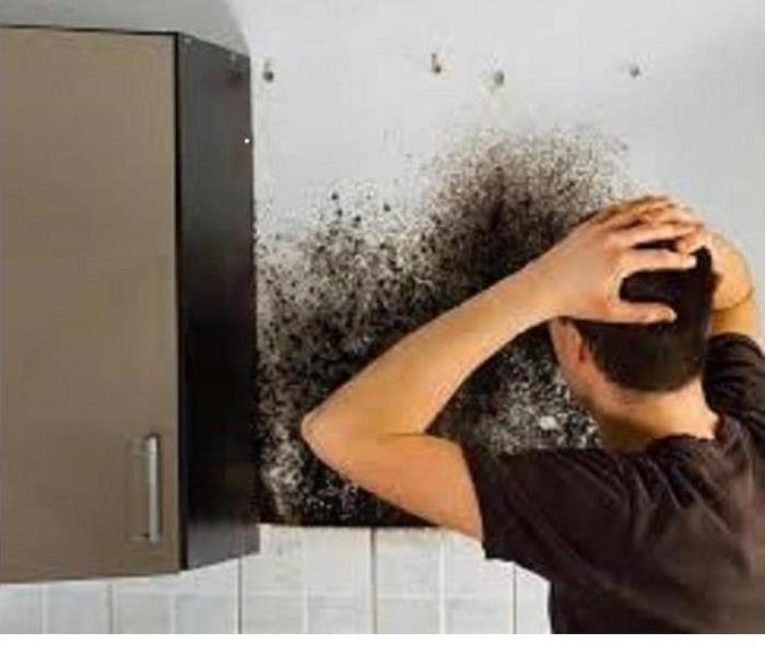 Man standing with his back to you with his hands on his head looking at mold on the wall