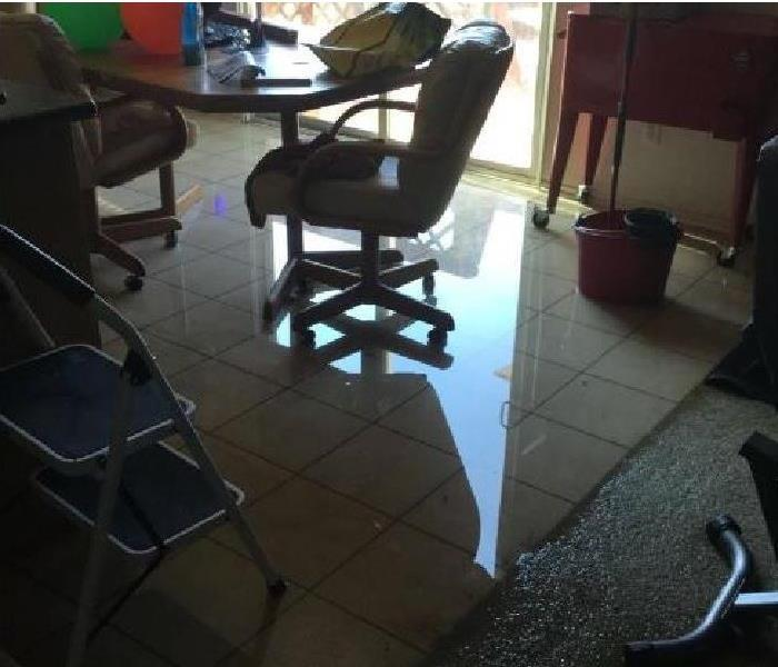 Standing water remains in a kitchen home after a water loss.